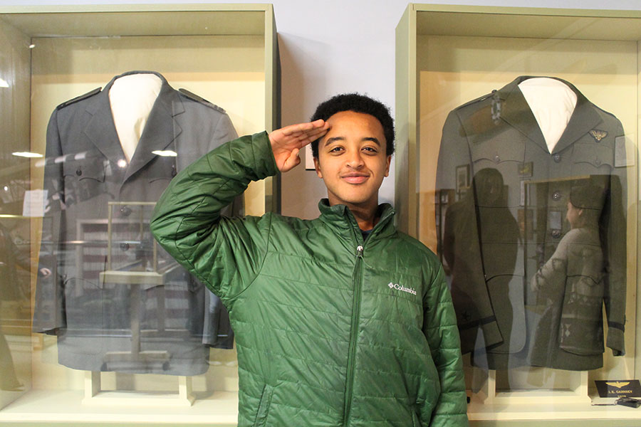 Cooper Murray '20 poses in front of military uniforms.