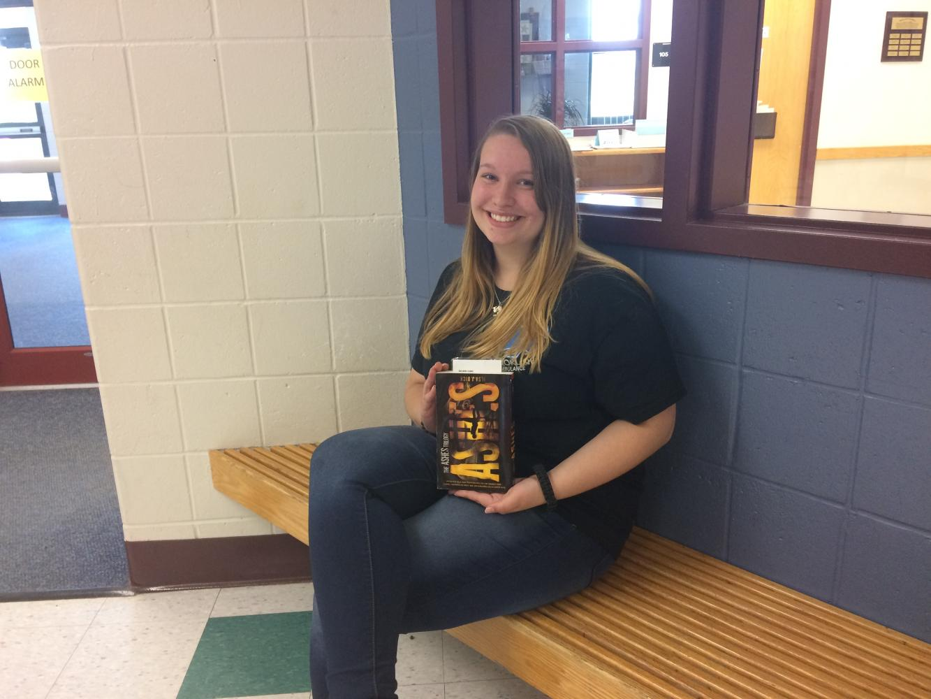 Ash Guthrie '19 poses with the dystopian thriller novel.