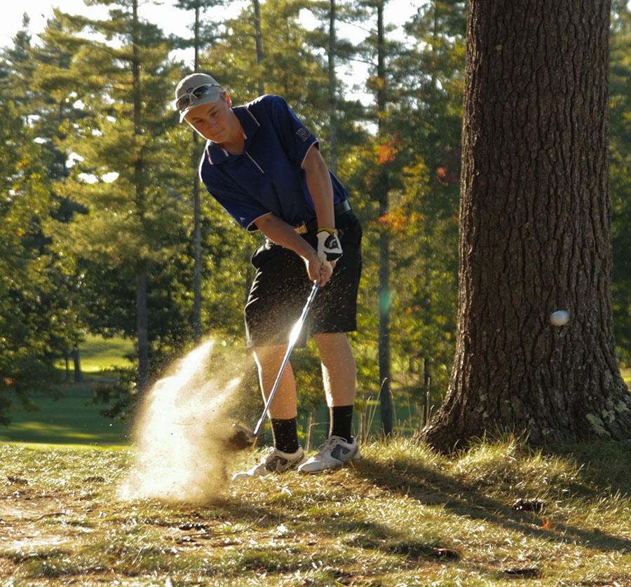 Golfer Ian McNamera chips out of the rough