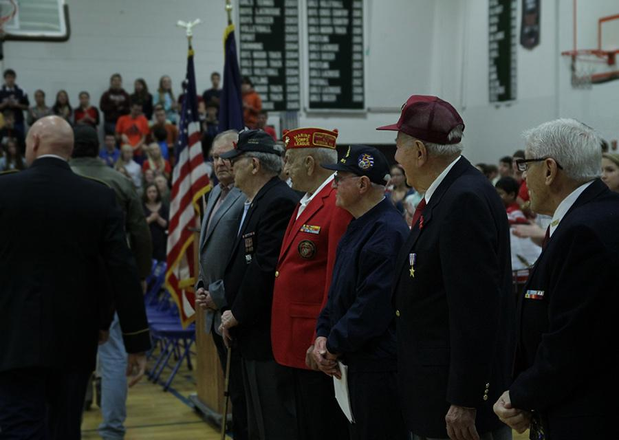 Veterans standing in respect for others coming in.
