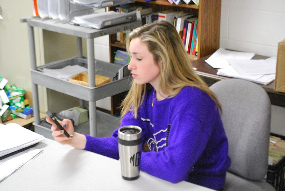 Mollie Gillis, '14, scrolling through her phone and wearing her sweater on Tuesday