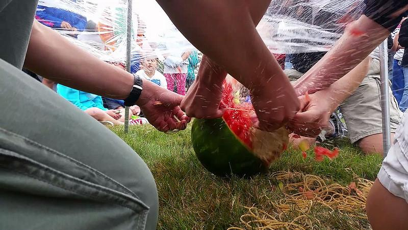 Members of the Robotics team pass time by crushing a watermelon with rubber bands.