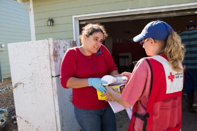 Thursday, September 19, 2013. 37th Street and Riverside Parkway in Evans, Colorado. Fatima Payan, of Evans, Colorado, happily accepts the gloves, masks and garbage bags from emergency response driver Tameln (Tammy) Self, of Hutchinson, Kansas, to assist her with the cleanup to her home. Photo by Hector Emanuel/American Red Cross