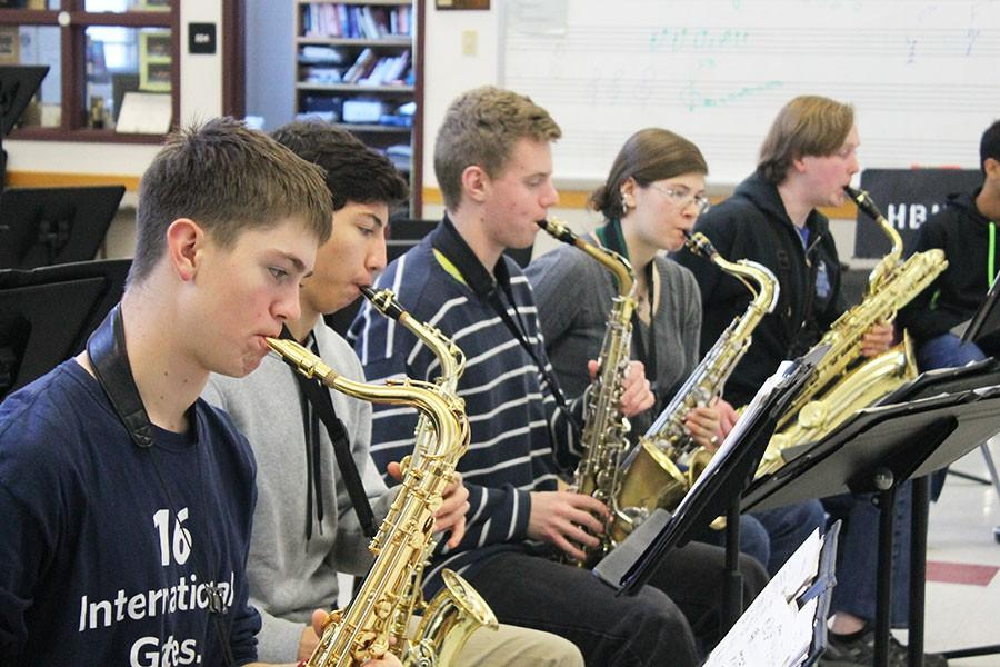 The saxophonists practice their part together