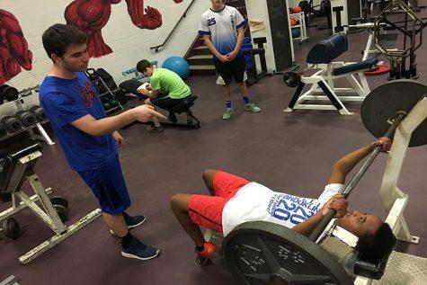 Senior Evan Sutton coaches Freshman Cooper Murray on how to do a chest press.