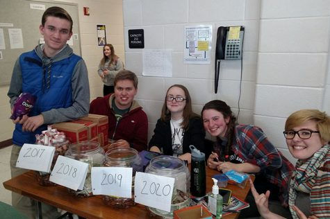 Students sitting with the class jars on the last day of Penny Wars. From left to right: Nathan Buckley '17. Chris Aulbach '17, Caitlin Ross '17, Audra Paradie '17, and Abby Lewis '17.