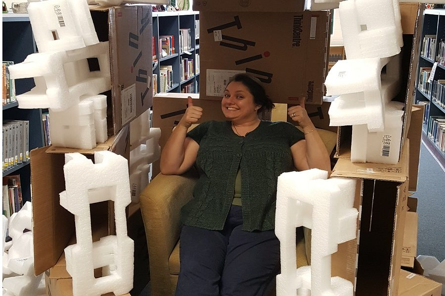 Librarian Christine Heaton posing on the throne of her box fort.