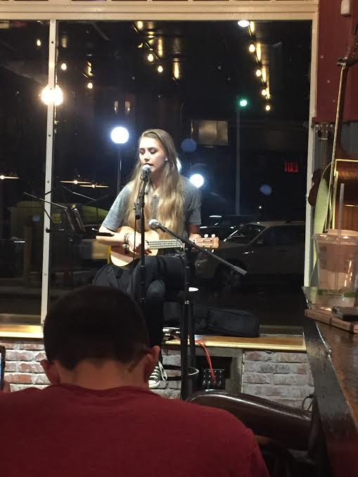Brianna DeJoie strums her ukelele and sings for the crowd.