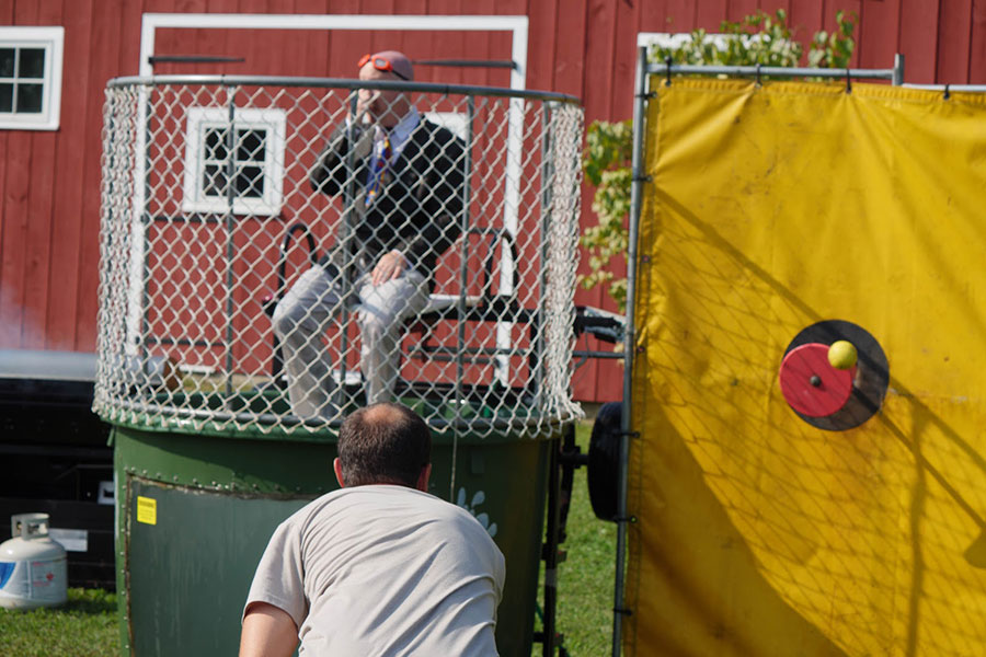 "Adam Wilcox dunks fellow physics teacher Eric Perry at the Senior Class Booth. Volunteers in the dunk tank included HBHS teachers, HBMS Principal Bob Thompson, and high school SRO Rick Bergeron. When asked how successful the fundraisers was, senior class advisor Tracy Gray said, ""I think this was one of our best ones yet."""