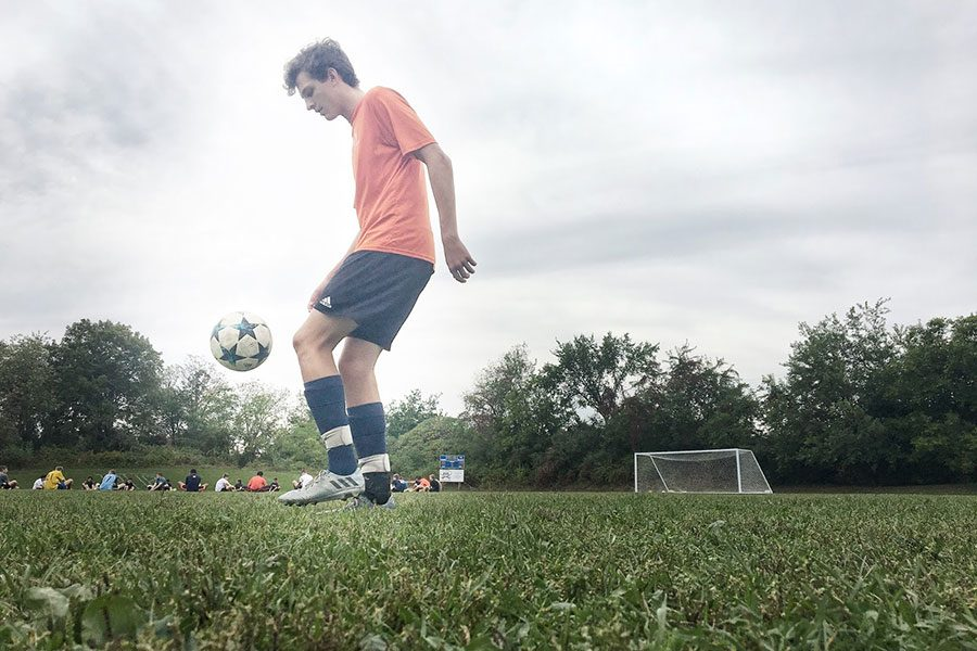 Jonathan Brackett '18 warms up on the sidelines, juggling his soccer ball to get loose. He has been known to juggle for thousands of touches in a row, and it translates to great control and skill on the field. Brackett said he's excited for college soccer, and he cannot wait to continue his career.