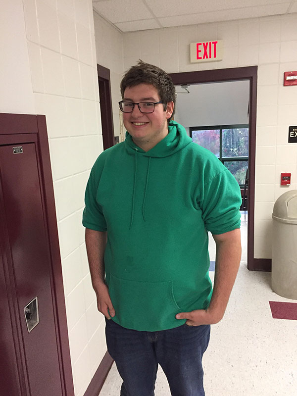 """Pugh smiles for the camera as he stands in the hall. """"I look forward to the festival in February,"""" he said with regards to the eventual Jazz All-State performance."""