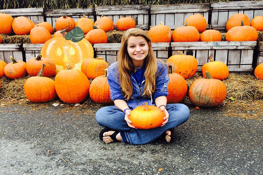 "Pumped, student Rachel Romanow '18 lifts a pumpkin, excited for Halloween. She went pumpkin picking for the perfect pumpkin to carve. ""I like this one. It's spooky Mitchell!"" said Romanow."