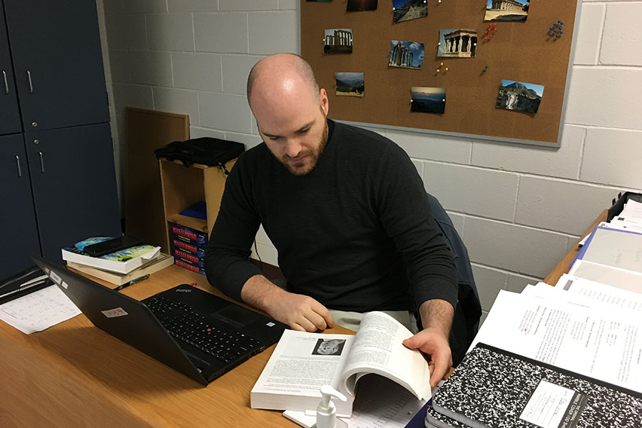 "New Latin teacher Matt MacFarline sits at his desk, preparing for the day ahead of him. ""I love it here at HB...I chose Hollis Brookline because of the community. There's this really strong bond here between the students and the faculty. The students all want to learn here. I didn't always get that same feeling in other areas,"" said MacFarline."