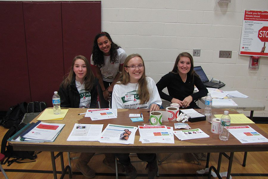 "A group of students helps out at the school's November blood drive in 2013. The Red Cross Club is known for a multitude of events throughout the year beyond blood drives, from safety training to card-writing for American troops overseas. Members of the community would like to see even more events and involvement in the future. ""Through a more widespread participation from the school, [Red Cross] would make a bigger impact, but, right now, it is an isolated entity that acts on its own,"" says Jack Aldana-Proulx '18. He hopes to see more events in the future."