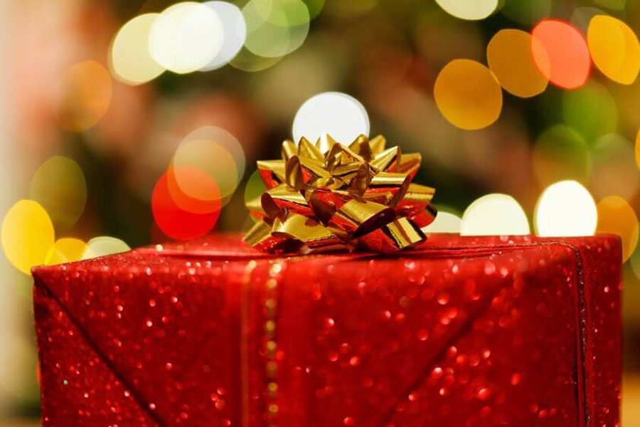 A+neatly+wrapped+gift+sits+below+the+traditional+Christmas+tree+and+waits+to+be+opened+on+Christmas+day%21