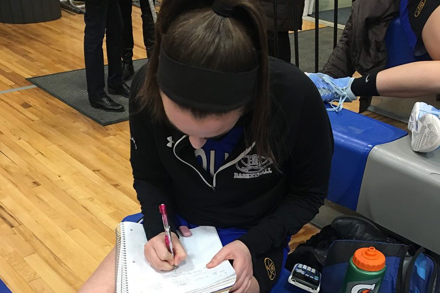 """Joanna Balsamo '18 vigorously grinds out her homework before a crucial basketball game. This picture was taken at Pelham High School only a half hour before the tip. """"Getting back late at night with tests the next day and having to study late into the night makes it difficult"""", says Balsamo."""