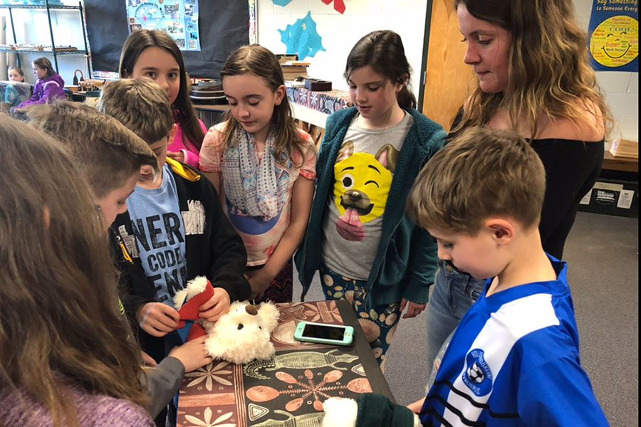 Students learn how to wrap wounds using a stuffed animal.