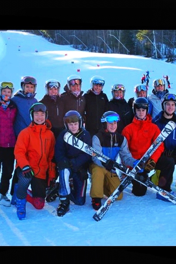 """Both the Hollis Brookline Boys' and Girls' Alpine Ski Teams pose for a team picture on the snow at Sunapee Ski Mountain and Resort. At the Sunapee competition, the girls' team had one of their sweeping wins, coming in first place overall. While that win was incredible for the team, both the boys and girls teams said that it was the teamwork that lead them to every success. """"The dynamics of the team improved a lot and we became a lot closer,"""" said Lysik."""