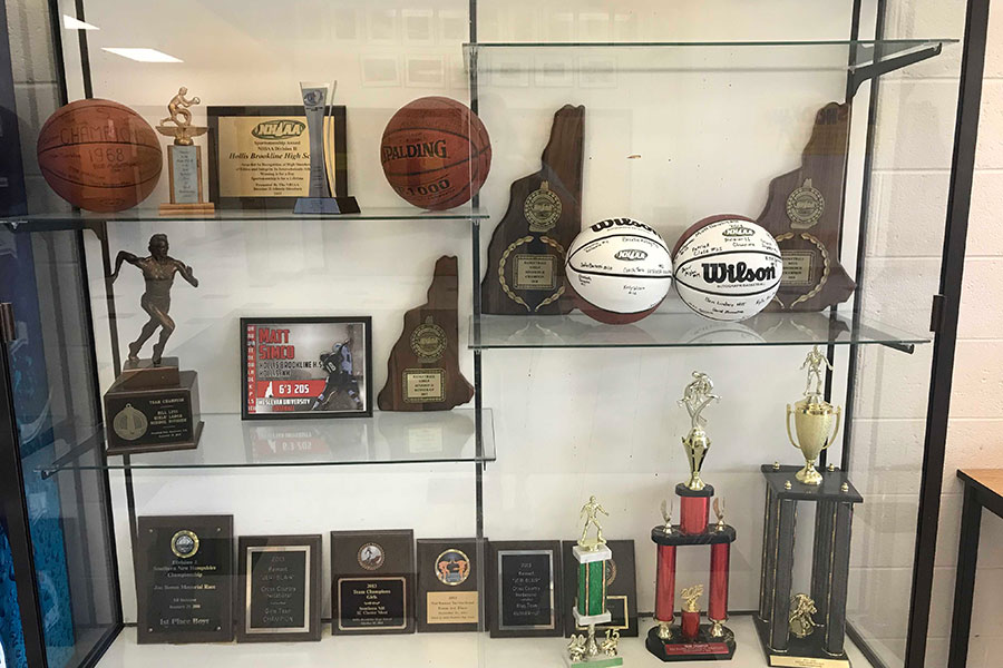"The D2 Hollis Brookline Girls Basketball team is looking to add to the collection of basketball fame for the school. This glass showcase is located in the back lobby in front of the gym holding the previous trophies and plaques for both girls and boys basketball. ""Fortunately, we played our best team basketball in the playoffs,"" said Murphy."