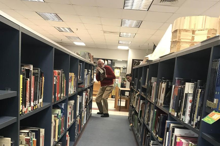 "Mike Fox and Christine Heaton pose at the end of the school library aisle. Fox is holding a handful of classic novels while Heaton stands at the end of her beloved bookcase. ""What's the difference between reading a magazine and article posts on Facebook?"" said Heaton."