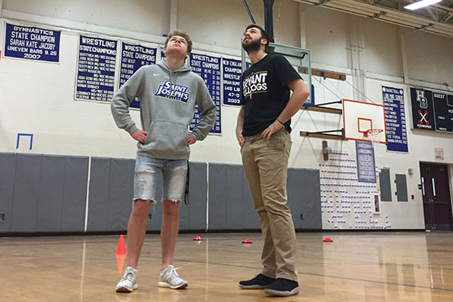 "Jonathan Brunkhardt '18 and Scott VanCoughnett '18 gaze bitterly at the softball and baseball batting cage, located on the ceiling in the gymnasium. The volleyball teams have claimed that the low-lying cage gets in the way of their games. ""It sucks,"" says Burkhardt."