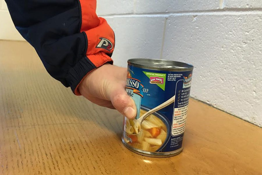"Jack Sinclair '19, manager for the Girls Volleyball team, donates a can of soup to the NH Tackles Hunger food drive. Through this food drive, students across the state are able to help stock local food banks. Donations from Hollis Brookline athletes and fans are brought to the Milford food bank. ""It's always important to participate in your municipal community, but your geographical as well,"" said Sinclair."