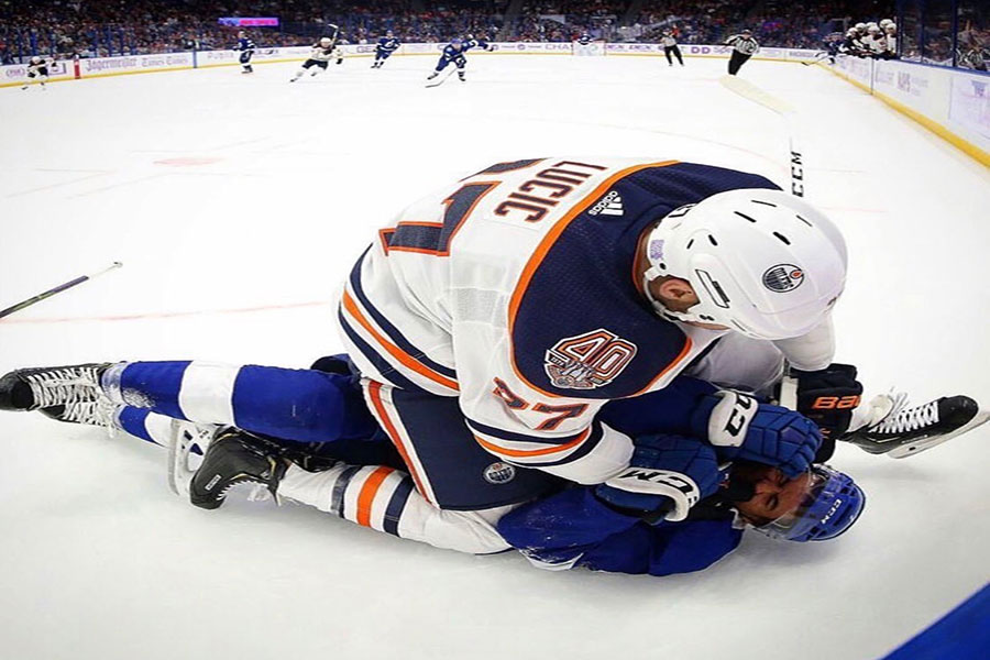 "Milan Lucic #27 sits on, rookie, Mathieu Joseph after checking him. The hit cost Lucic a 10 minute penalty and $10k. ""Part of the reason we have Looch [Lucic] here is to take care of teammates, and he did that,"" said Todd McLellan who is head coach of the Edmonton Oilers."