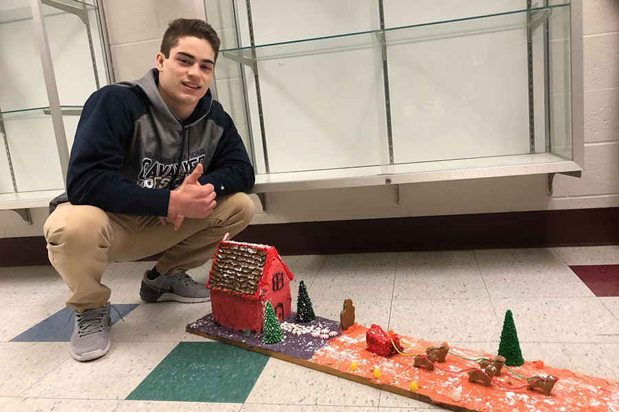 "Scott Anneser '19 stands next to his gingerbread house, a project assigned in Foods class at HBHS. ""The making of the gingerbread house combined teamwork, friendship, and hard work with making food and learning. ...we learned to problem solve and persevere through all the adversity. It was a great experience,"" said Anneser."