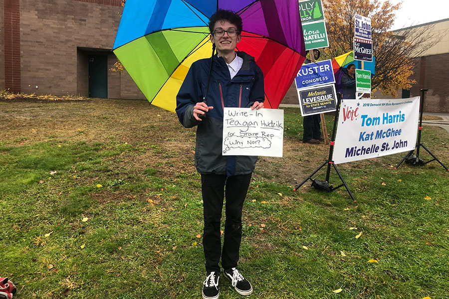 "Teagan Hudzik '19 stands outside the polling station in Hollis, campaigning for himself as a representative write-in. Although Hudzik was aware he was extremely unlikely to be elected, his stand showed that he took interest in the civic functioning of the United States government. ""It's important to let your voice be heard. The whole cornerstone of our democracy is about participation in elections...Young people are very much so underrepresented in electoral politics and it's really vital that their voice be heard… everyone's voice deserves to be heard."""