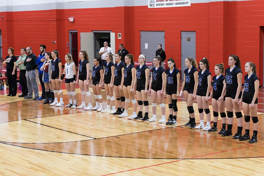 The varsity volleyball team stands united for one of their last games in their high school careers. Looking closely you can see the players linking hands, uniting them before they step out to the court.