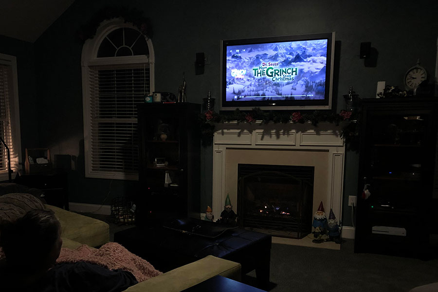 "A holiday movie enthusiast watches How the Grinch Stole Christmas. Released in 2000, this movie is the second of three movies based on Dr. Seuss's How the Grinch Stole Christmas. ""It's just a really touching story, and it has a great soundtrack,"" said Ashlyn Mansfield '19."
