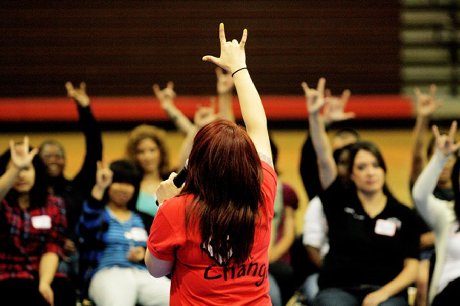 A Challenge Day ambassador raises her hand in unison with students at an assembly.