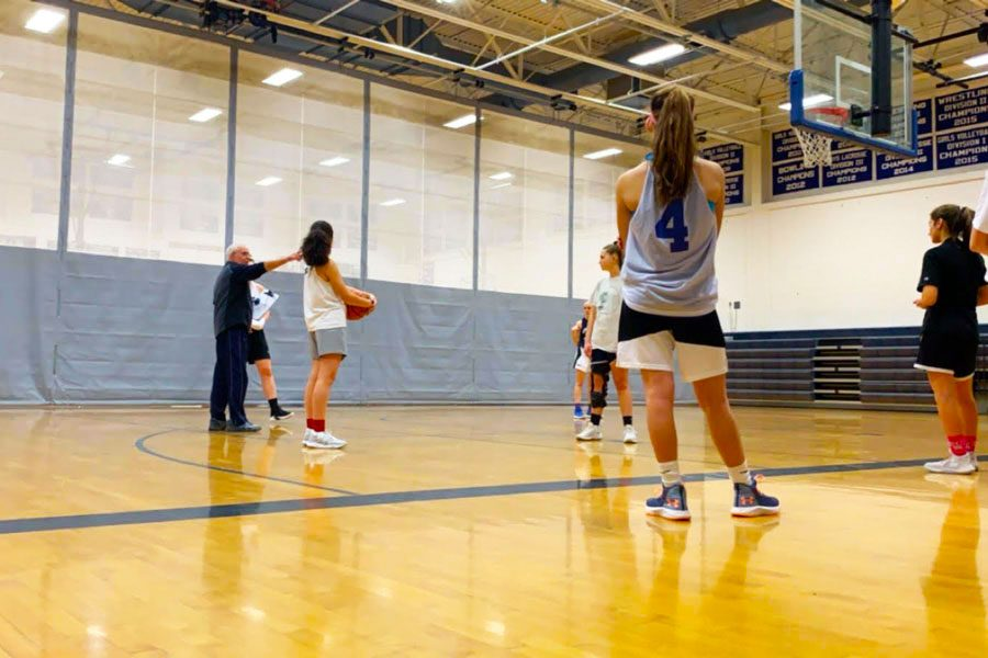 """The girl's basketball team practices in the gym. The team has a 7-2 record and each girl has a commitment to play the sport. """"I have learned to channel my aggression into playing whether it be hitting the ball harder in volleyball or going up stronger to the hoop in basketball,"""" said Elizabeth Atkinson '19."""