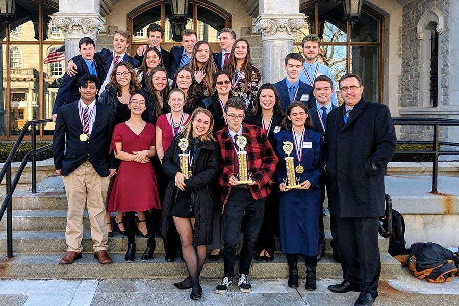 "Students in HBHS's AP U.S. Government class stand outside of the NH Legislative Building after winning their district hearing. Out of the six units of the We The People text, HB got the highest score for three units, qualifying them to move to the state level. ""[Students are] always very competitive,"" said AP U.S. History teacher Trevor Duval. ""I'm always impressed by their depth of knowledge and understanding.""    First Row (left to right) Rachel Ash '19, Teagan Hudzik '19, Kay Partridge '19, AP US Government teacher Trevor Duval Second Row: Zaki Quereshy '19, Tess Crooks '19, Cordelia Scales '19, Nicole Plummer '19, Robbie Dwyer '19 Third Row: Rachel Cerato '19, Caroline Smith '19, Jillian O'Hara '19, Jacob Ponders '19 Fourth Row: Maya Ruvido '19, Myah Caplan '19, Emma Pellerin '19, Tristain Hoenninger '19 Fifth Row: Jack Sinclair '19, Joe Caswell '19, Madoc Lewis '19, Alex Dougherty '19, Kyle Swope '19"