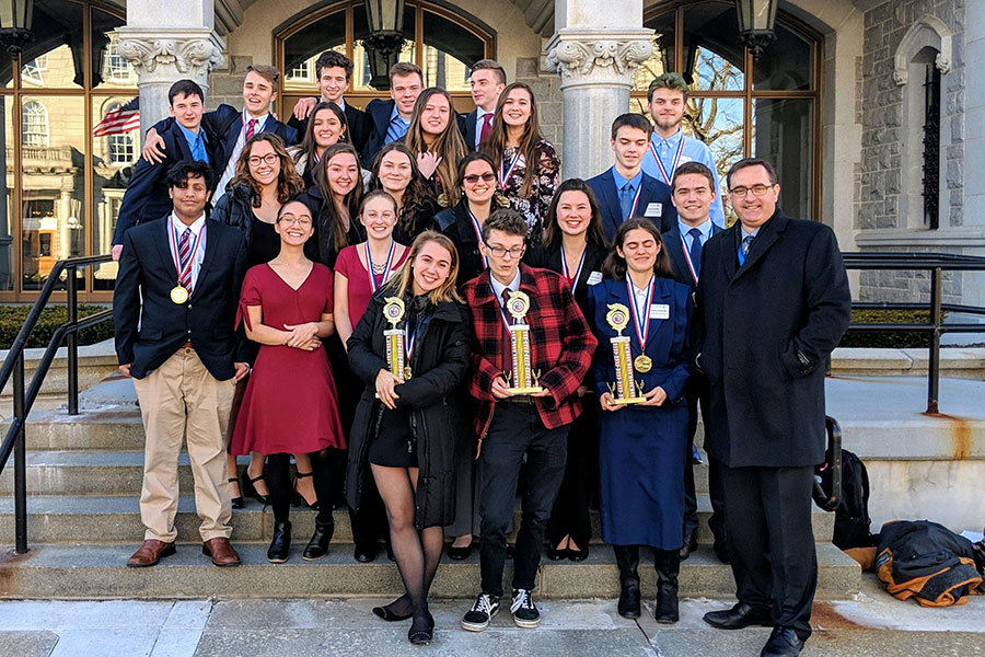 """Students in HBHS's AP U.S. Government class stand outside of the NH Legislative Building after winning their district hearing. Out of the six units of the We The People text, HB got the highest score for three units, qualifying them to move to the state level. """"[Students are] always very competitive,"""" said AP U.S. History teacher Trevor Duval. """"I'm always impressed by their depth of knowledge and understanding.""""    First Row (left to right) Rachel Ash '19, Teagan Hudzik '19, Kay Partridge '19, AP US Government teacher Trevor Duval Second Row: Zaki Quereshy '19, Tess Crooks '19, Cordelia Scales '19, Nicole Plummer '19, Robbie Dwyer '19 Third Row: Rachel Cerato '19, Caroline Smith '19, Jillian O'Hara '19, Jacob Ponders '19 Fourth Row: Maya Ruvido '19, Myah Caplan '19, Emma Pellerin '19, Tristain Hoenninger '19 Fifth Row: Jack Sinclair '19, Joe Caswell '19, Madoc Lewis '19, Alex Dougherty '19, Kyle Swope '19"""
