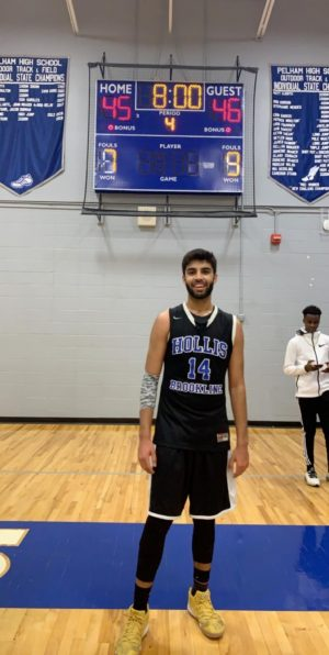 """Dhruv Miglani '19 stands proudly in front of the score board at the end of his career boosting game. Miglani has a fantastic game with 19 points on the night. """"I don't think I'm ever going to forget hitting that shot,"""" said Miglani."""