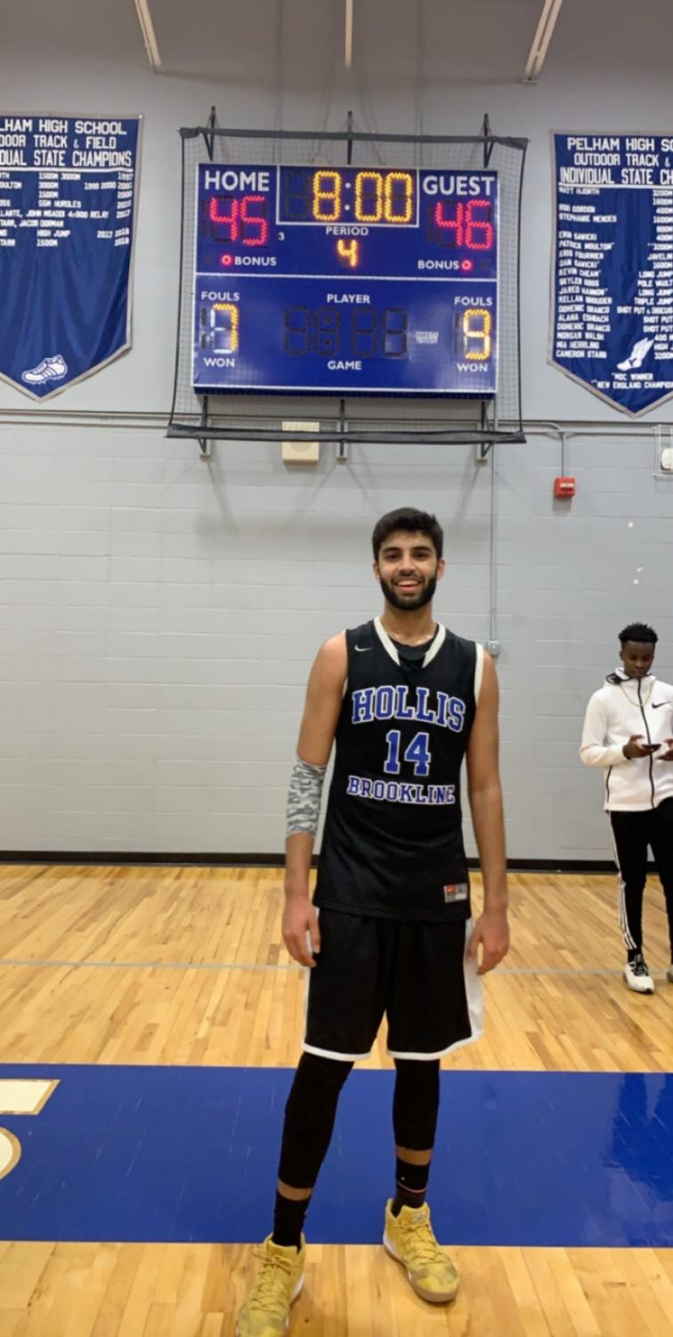 "Dhruv Miglani '19 stands proudly in front of the score board at the end of his career boosting game. Miglani has a fantastic game with 19 points on the night. ""I don't think I'm ever going to forget hitting that shot,"" said Miglani."