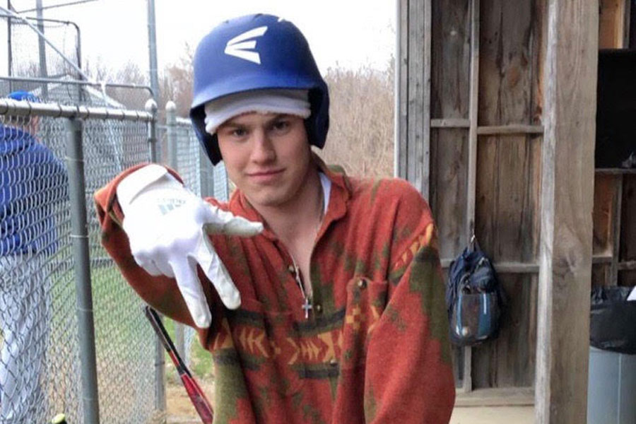 """Joe Messina, gearing up for his next game against Coe-Brown in the HB dugout. The boys continue their winning season. """"I love baseball,"""" said Joe Messina '19."""