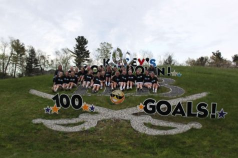 "The girls lacrosse team celebrates after Sweeney recorded her 100th career goal. The ""countdown"" was at 98 entering the game against Keene on May 9, but fans didn't have to wait long for number 99 and 100. ""The milestone came as a pleasant surprise,"" said Sweeney."