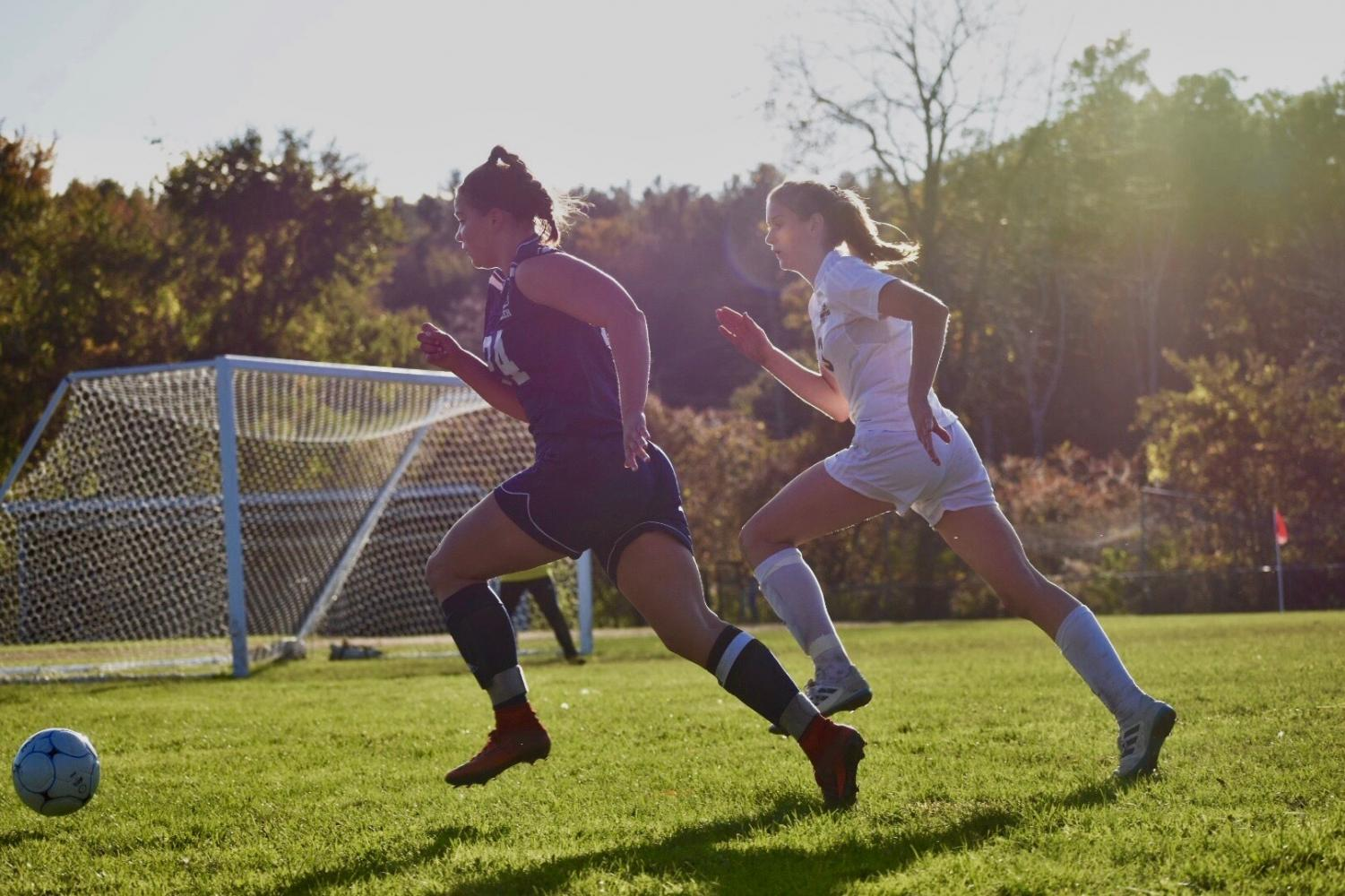 """Tasha White '20 during a 2018 regular season game against Souhegan, chasing the ball as she approaches goal. This is the third season she has been a starter for the Hollis Brookline Varsity girls soccer team. """"We have the full potential everywhere on the field to make playoffs, even if someone is not there,"""" said White."""