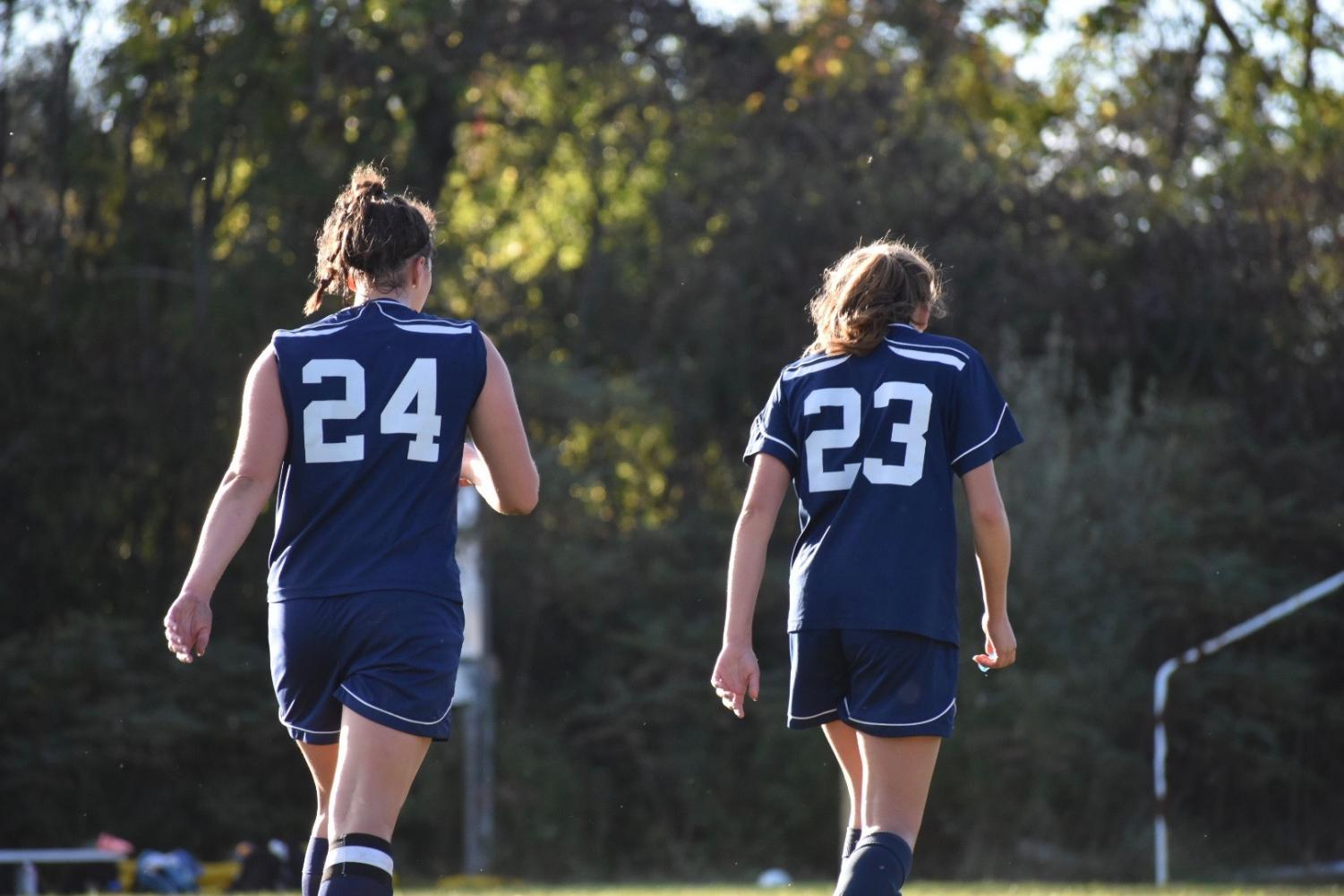"Tasha White and Rachel Brackett heading time the bench after a 2018 game against Souhegan. This is White's fourth year on Varsity as a senior and Brackett's  second as a sophomore. ""We have girls that can play any position and well and that's not common, it's great to have a solid team on the field and even on the bench because you never know what will happen,"" said White."