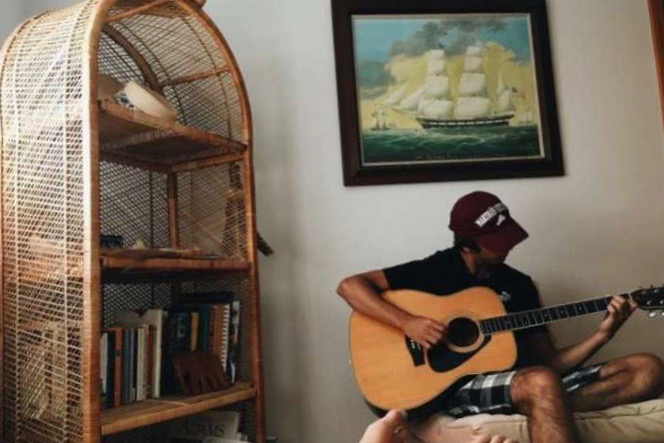 "Jack Delaney plays his favorite acoustic guitar in Martha's Vineyard. Jack started playing his sophomore year and has fallen in love with the instrument. ""I'm proud that he is doing what he wants to do,"" said Marc-Andre Thermitus 21'."