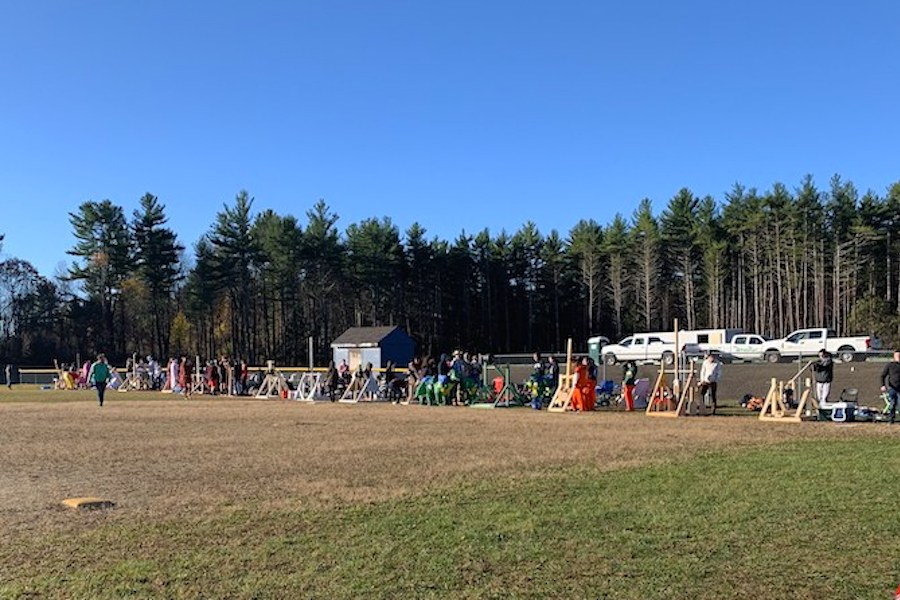 """The students lined the softball field as they test their final trebuchet constructions. The kids had over a month to prepare for such a feat and, even though stressful, it was still exciting. """"Our group has had a lot of fun designing it and going through the process,"""" said Plummer."""
