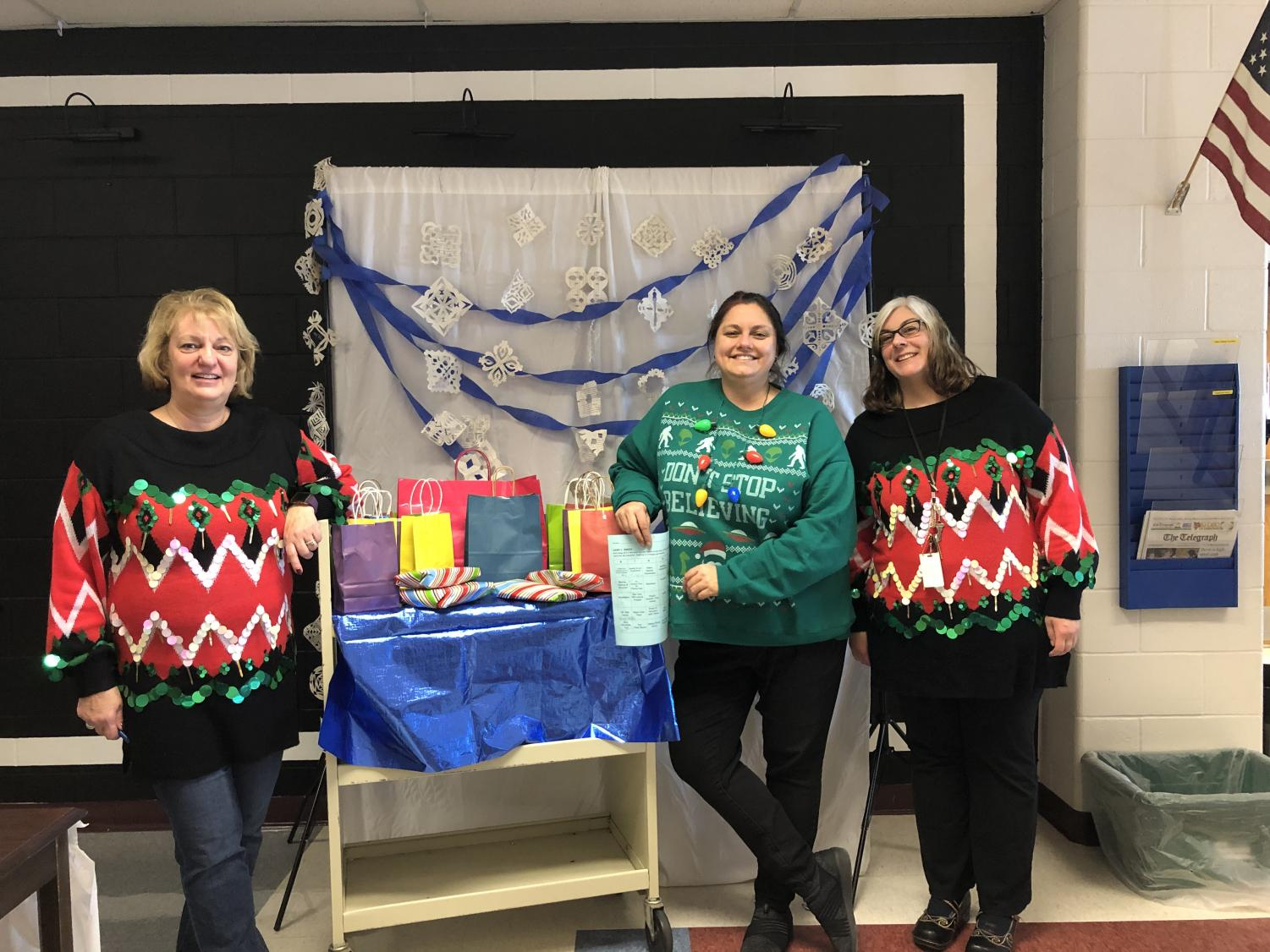 (From left to right) English Teacher Marie Salamone, Head Librarian Christine Heaton and Library Aid Alana Taylor stand in front of the Sweater Day prize cart.  The second annual Sweater Day was a success! Enjoy the holiday break, HB!