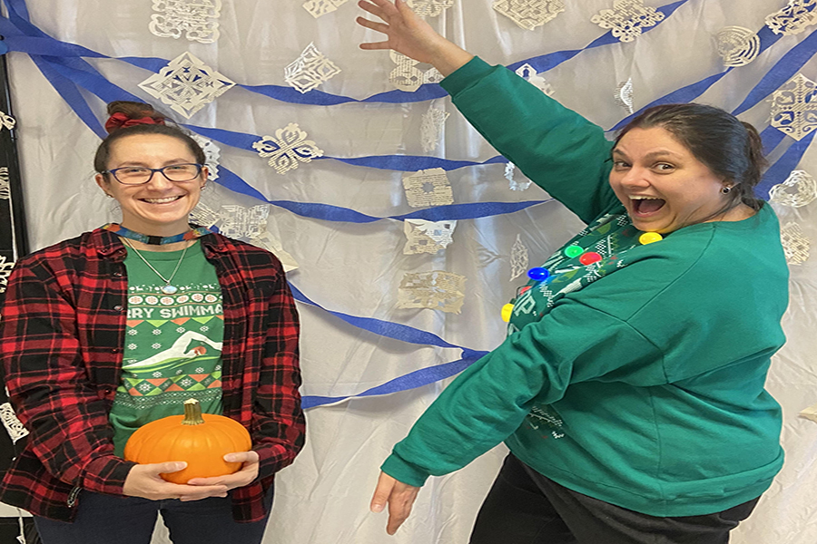 """Mrs. Heaton and Mrs. Saunders in the library taking a holiday photo The teachers pose for a picture celebrating holiday break. Being with family is really the most important thing"""" said Ellie Jordan 20."""