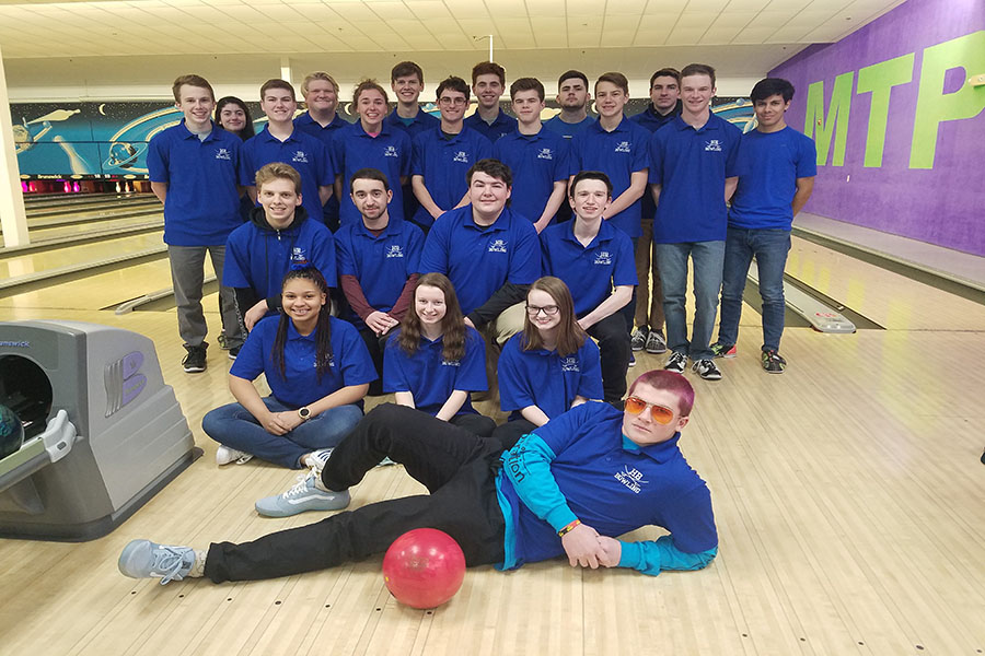 "The bowling team poses after a competition. Many members of the team have been together since freshman year. ""I've coached other teams, other sports, and the team was really good but they didn't get along and we didn't win,"" said Coach D'Attilio. ""I'd rather coach a team like this that gets along. And to boot, they're also winning."""