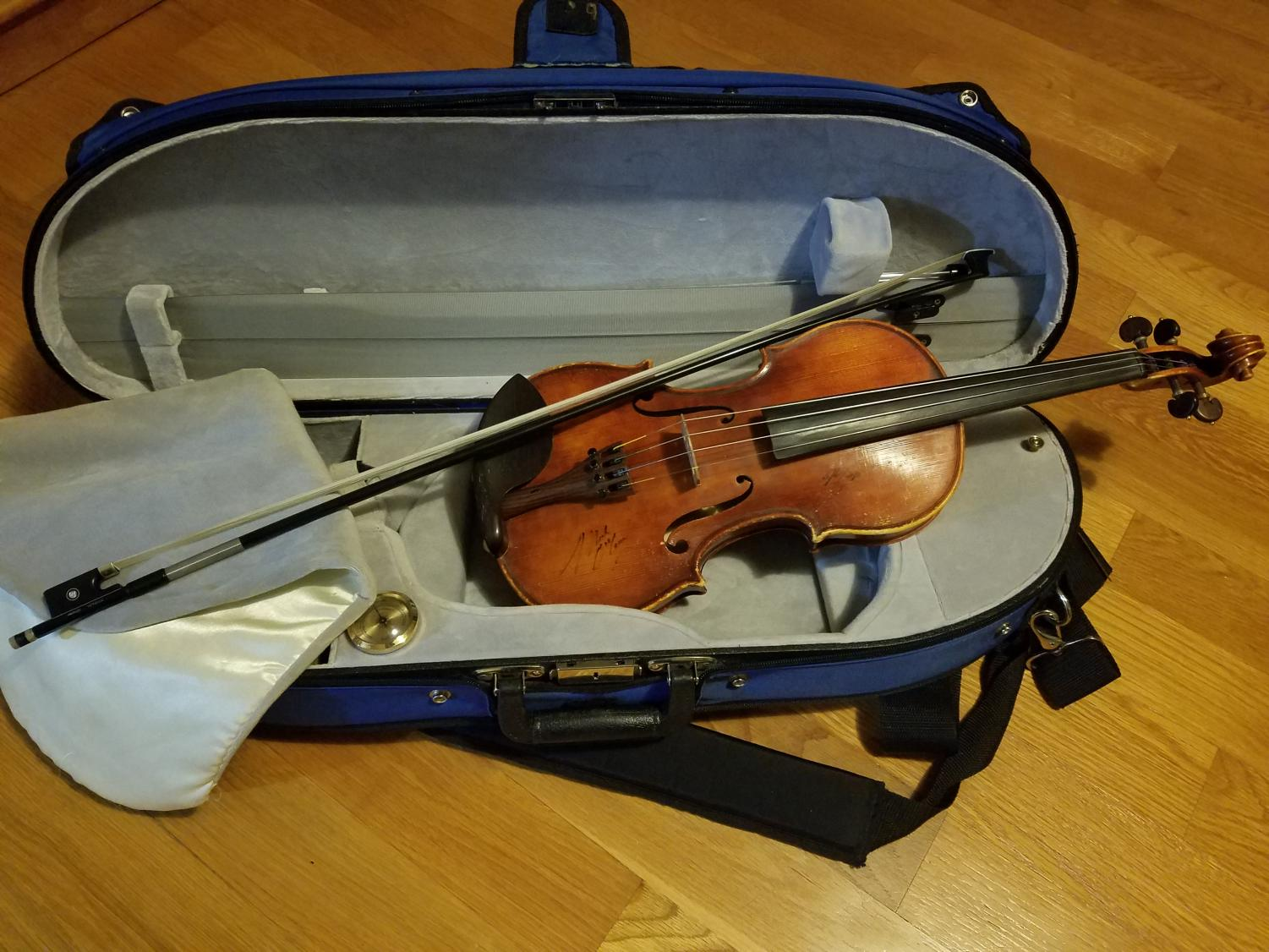 """A violin sits in its case, waiting for an eager student to play it. The lack of strings-related ensembles or classes has caused many complaints among strings musicians. """"Unless the kids have private teachers or are already a part of a different ensemble, it is hard to maintain playing the instrument because there is nowhere for them to play it,"""" said Claudia Pack '22."""