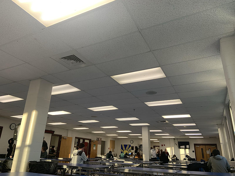Pictured+is+the+school+cafeteria+where+many+students+dine+and+study+under+the+brightly+lit+fluorescents+of+the+school.+%E2%80%9CFluorescent+lights+make+me+feel+like+I%E2%80%99m+in+a+hospital+and+it%E2%80%99s+not+fun%2C%E2%80%9D+said+Mike+Vinton+%E2%80%9822.