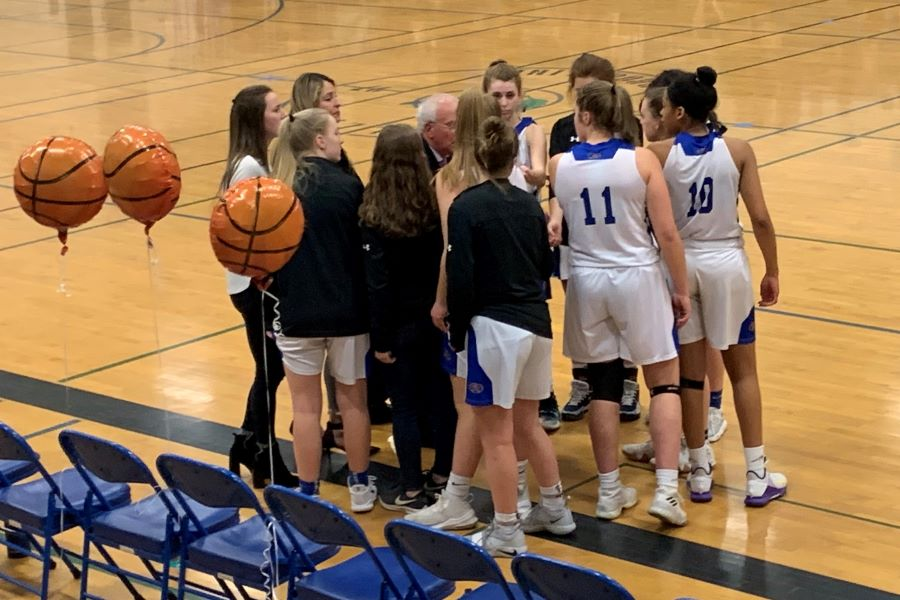 "The girls team surrounds Coach Bob Murphy, reviewing their game plan. The girls need to ""go in strong, playing our game, moving the ball more"" said Amanda Goclowski '20 as they head into their game against Kearsarge."