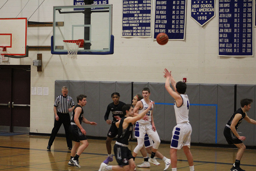 "Matt Dias '21 at, attempting a 3-point shot against Hanover. Dias led the team in points to a victory, 70-63. ""We knew going in that Hanover was probably the best shooting team we were going to play all season, so it was key that we closed out their shooters and sprinted back on defense,"" said Dias."